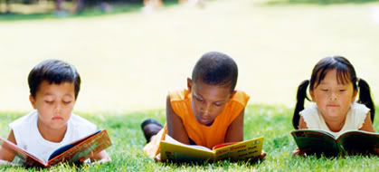 Three children reading outside.
